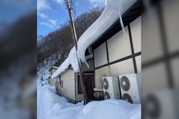 雪の重みにより傾いた電柱