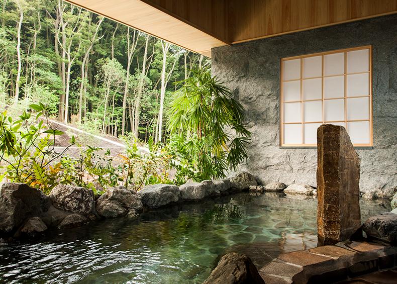 緑が映える石造りの大浴場。外の自然との一体感の中で温泉をお楽しみいただけます。
